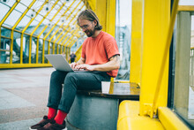 Happy Guy Browsing Laptop In Pedestrian Bridge