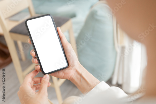 Fototapeta cell phone blank white screen mockup.woman hand holding texting using mobile on desk at office.background empty space for advertise.work people contact marketing business,technology obraz