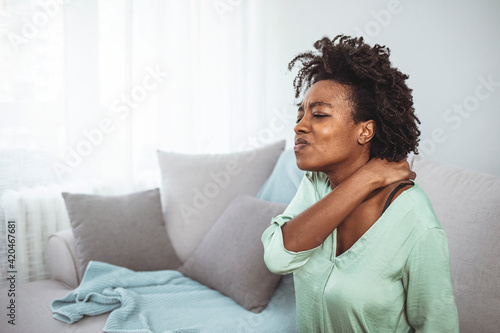 Beautiful young woman keeping hands on her neck, feeling pain, sitting on bed at home. African young woman have neck ache. Cropped shot of a businesswoman suffering from neck pain