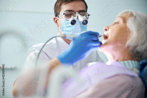 Fotografie, Obraz Dentist in dental headlights loupes treating old woman teeth