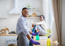 Positive Black Guy Using Detergent For House Cleanup, His Girlfriend Sitting On Kitchen Table, Copy Space