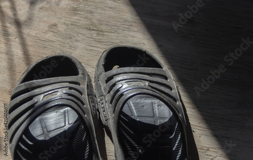 Obraz old, worn black sneakers on the floor - fototapety do salonu