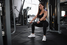 Attractive Young Sportswoman Doing Squats In Crossover Gym Machine, Copy Space