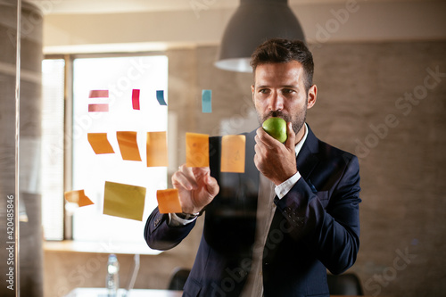 Businessman in conference room eating apple. Young businessman having healthy snack.