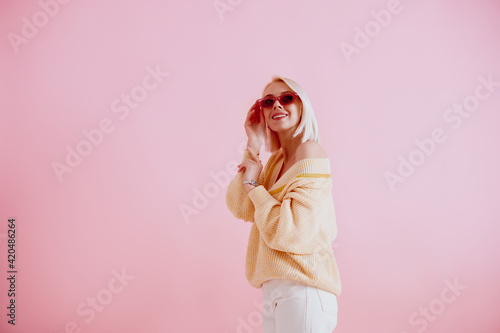 Obraz Happy smiling lady wearing trendy pink sunglasses, yellow  sweater, stylish silver wrist watch, posing on pink background. Spring fashion conception. Copy, empty space for text  - fototapety do salonu