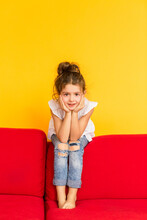 Little Cute Girl With Dark Hair In A White Blouse And Jeans Sits On A Red Sofa On A Yellow Background. Little Girl Grimaces