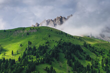 A Green Hill With A Rocky Peak And Clouds In The Background