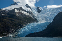 A Sailboat Floats In Front Of Huge Glaciers Leaping Into The Sea
