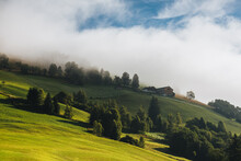 Green Hill With Trees And Houses Covered In Fog And Clouds