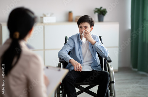 Obraz Professional psychologist working with disabled teenager in wheelchair at office - fototapety do salonu