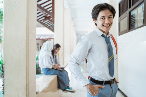 Fototapeta a high school boy smiles at the camera wearing a school bag in the background of