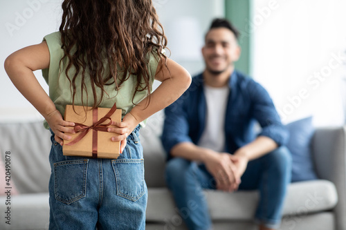 Fototapeta Little girl greeting her dad with Fathers Day, holding gift behing back