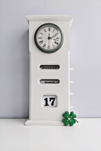 Wooden White Vintage Clock With Calendar And Saint Patrick's Day Cloverleaf On Grey Background
