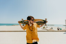 Young Man With A Longboard In Front Of The Beach