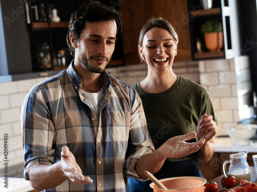 Fototapeta Husband and wife in kitchen. Young couple preparing delicious food at home. obraz