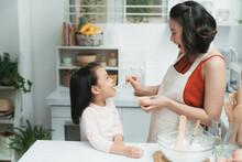Asian Mother Feeding Her Daughter Flan.