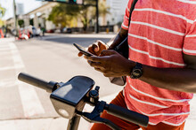 Black Man Unlocking An Electric Scooter To Move Faster