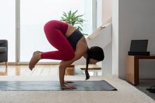 Woman Practicing Crane Pose At Home
