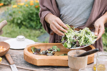 Anonymous Hand Making Fresh Salad With Wildflowers