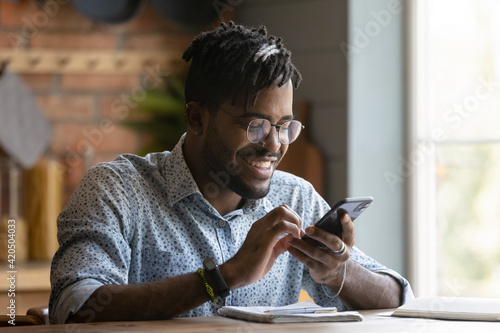 Fotografia Happy young african american man hipster sit at table in cozy cafe use phone app for work study communication