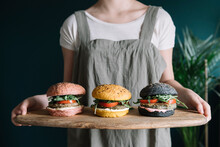 Young Woman Holding Three Colorful Vegan Burgers