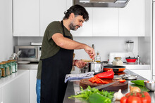 Male Cooking In A Modern And Bright Kitchen