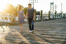 Couple Walking On A Dock By Fishing Boats