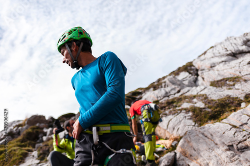 Focused young climber belaying partner in daytime