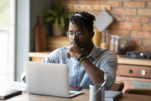 Freelancer At A Job. Young African Man Hipster Think By Laptop At Home Office Prepare Report Electronic Document Use Open Source Web App. Focused Black Male Student Read Web Search Result On Pc Screen