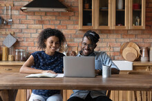 Friendly Afro American Married Couple Study From Home Using Laptop Watch Webinar Training Master Class Together. Motivated Young Black Husband Wife Take Part In Massive Open Online Courses By Internet