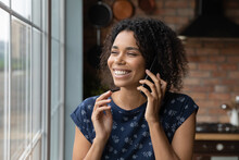 Glad Young African Ethnic Woman Talk On Telephone Call From Home Stand By Window Hold Device To Ear. Happy Black Housewife Caller Enjoy Phone Conversation Chat With Friend Discuss Sale Share Good News