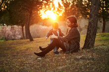 Mother And Baby Resting In Park At Sunset