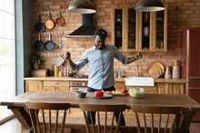 Cooking Food With Inspiration. Overjoyed Young Afro American Guy Hipster Dance By Kitchen Table Preparing Favorite Vegetable Meal. Active Millennial Black Man Having Fun Making Healthy Breakfast Lunch