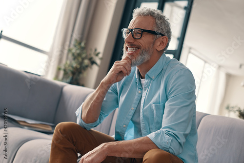 Side view of carefree senior man in casual clothing and eyeglasses holding hand on chin and smiling while resting on the sofa at home