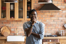 Happy Homeowner. Smiling Millennial African American Man Posing For Portrait At Modern Kitchen Interior. Successful Young Black Guy Hipster Just Moved In New Home House Look At Camera Enjoy Wellbeing