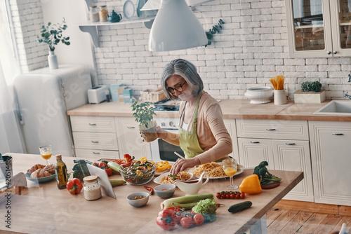 Top view of senior woman in apron cooking healthy dinner while spending time at Tapéta, Fotótapéta