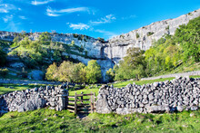 Malham Cove In The Yorkshire Dales With Blue Sky, Drystone Wall And Gate.