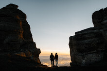 Couple Stands On Cliff And Looks At Dawn