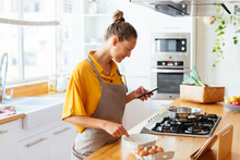 Smiling Woman Preparing Food And Texting On Phone In Kitchen