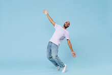 Full Length Young Cool Smiling Happy Funny Unshaven Black African Man 20s Wearing Violet T-shirt Hat Glasses Standing On Toes Leaning Back Dancing Isolated On Pastel Blue Background Studio Portrait.