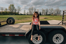 Girl Sitting On Trailer Pouting.
