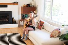 Teenage Girl Plays Acoustic Guitar In Living Room.