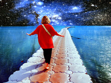 Surrealistic Collage. A Person Walks Along The Ocean Against The Background Of Stars And Galaxies