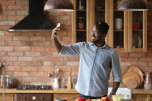 Obraz My culinary feats. Overjoyed afro caribbean male hipster shoot selfie on phone at home kitchen to share at social networks. Joyful young black male posing for self picture at moment of cooking food - fototapety do salonu