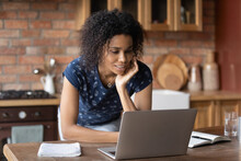 Young Mixed Race Female Working From Home Stand Leaning On Table With Pc Analyse Data On Screen Enjoy Training Video. Curious Black Lady Student Watch Webinar Online Solve Interesting Problem In Mind