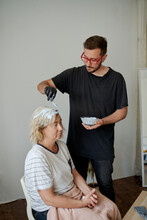 Adult Woman Dyes Bleached Hair At Home And Man Helping And Coloring Hair