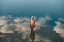Little Girl Standing In The Water Where White Clouds Are Reflected
