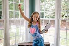 Beautiful Young Girl Dancing While Holding A Computer Tablet And Listening To Music