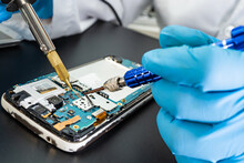 Technician Repairing Inside Of Mobile Phone By Soldering Iron. Integrated Circuit. The Concept Of Data, Hardware, Technology.