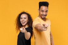 Young Couple Friends Together Team Family African Smiling Leader Man Woman In Black T-shirt Point Index Finger Camera On You Motivating Encourage Isolated On Yellow Color Background Studio Portrait